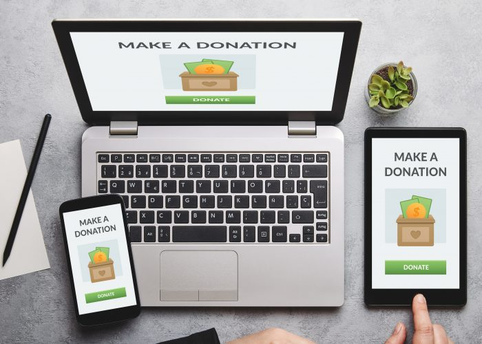 Donation concept on laptop, tablet and smartphone screen over gray table. Top view